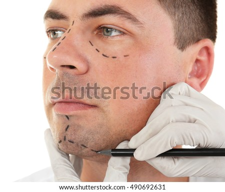 Plastic surgery concept. Hand in glove marking male face