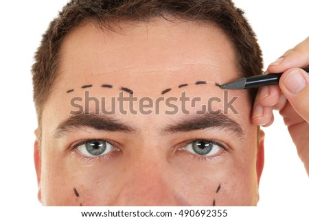 Plastic surgery concept. Hand marking male face