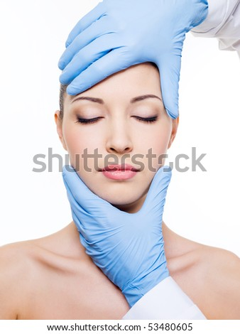 Plastic surgery touching the head of a beautiful female face with closed eyes - stock photo