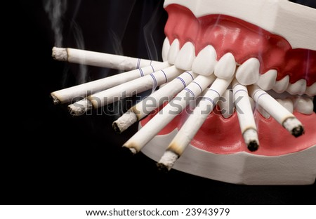 Plastic teeth with lots of cigarettes in the mouth on a dark background