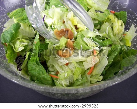 plastic tongs in fresh romaine salad with cashews