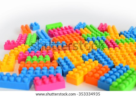 Plastic toy blocks on white background, selective focus - stock photo