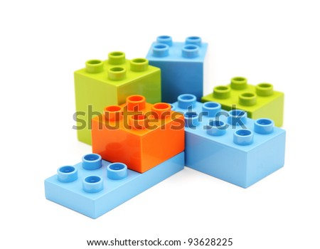 Plastic toy blocks on white. Focus on near edge of bricks with selective focus. - stock photo