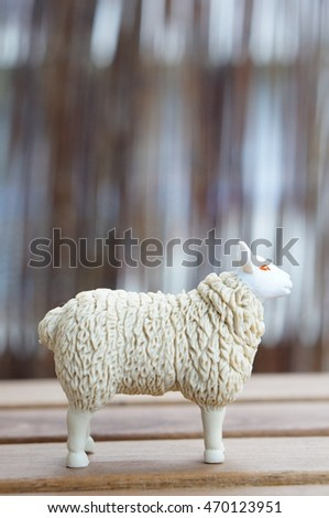 Plastic toy sheep standing on wooden table