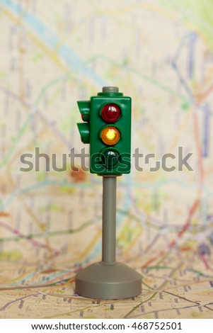 Plastic toy traffic lights with a yellow signal light on the map