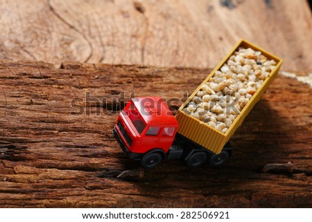 Plastic toy truck model red color with stone loaded represent the transportation concept related idea. - stock photo