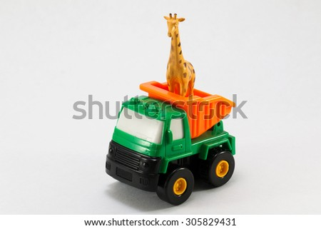 Plastic toy truck with a giraffe on a white background - stock photo