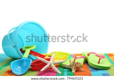 Plastic toys with beach towel on white background.