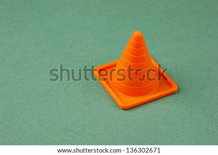 Plastic traffic cone on the green background