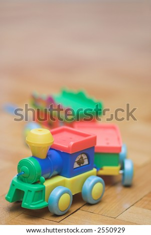 plastic train toy on parquet. shallow dof. space for text on top