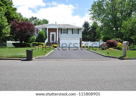 Plastic Trash Container on curb at driveway end of high ranch suburban home in residential neighborhood - stock photo