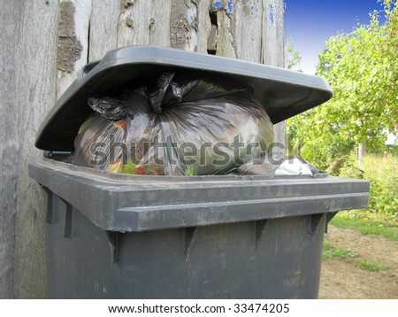 Plastic trashcan, full with the waste bags - stock photo