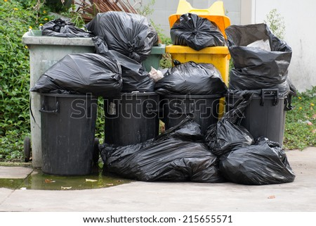 Plastic trashcan, overloaded with wastes and rubbish - stock photo