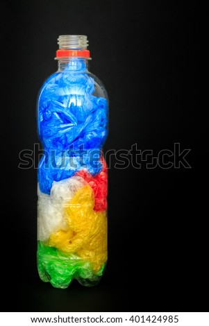 Plastic water bottle full of plastic shopping bags on black background. Concept image for polluting water and oceans with plastic waste. Copy space - stock photo