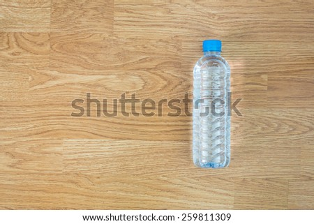 plastic water bottle on the wooden table background - stock photo