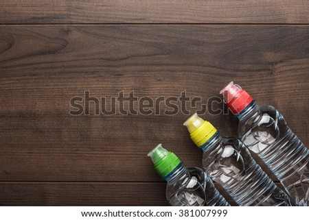 plastic water bottles with caps of different colour on the wooden table - stock photo