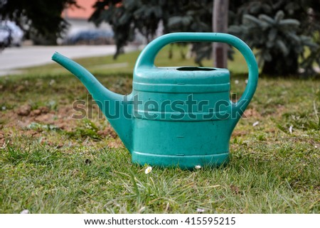 Plastic watering can in grass in the garden