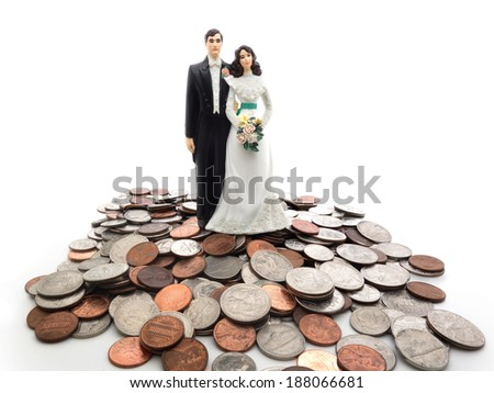 Plastic wedding couple on a pile of coins - money concept                                - stock photo