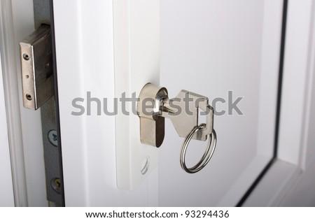 plastic white door, lock and key - stock photo