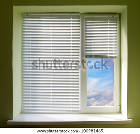 Plastic window blinds in the office with green walls. - stock photo