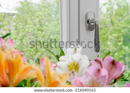 plastic window with flowers on windowsill - stock photo