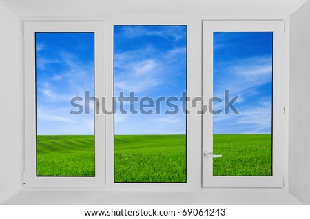 Plastic window with view to green field - stock photo