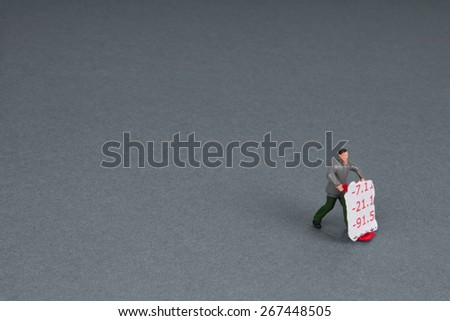 plastic workman figurine with a torn section of bank statement on a trolley. - stock photo