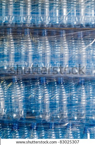 Plastic wrapping over finished water bottles in factory, warehouse industry - stock photo