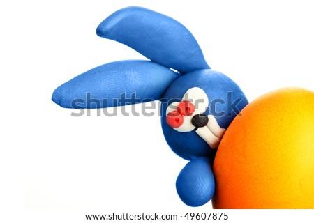 Plasticine rabbit with easter egg - stock photo
