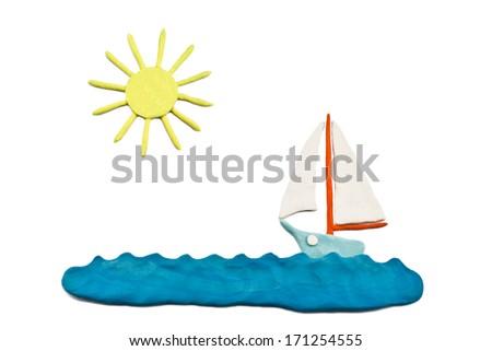 Plasticine sun, sea and sailing on his sailing ship - stock photo