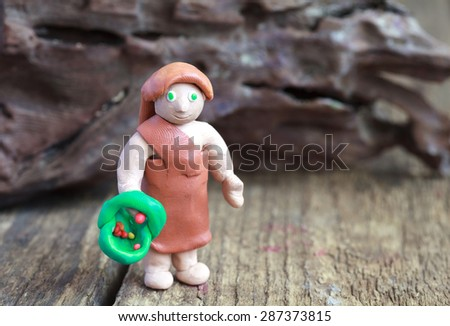 Plasticine world - a cave woman with a basket and berries, selective focus - stock photo
