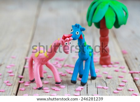 Plasticine world - little homemade blue giraffe with green spots and pink giraffe with orange spots with pink hearts on a wooden background, selective focus and place for text - stock photo
