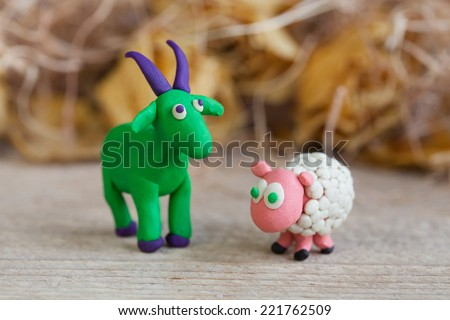Plasticine world - little homemade green goat with purple horns and hooves and sheep stands on a wooden floor, selective focus and place for text - stock photo