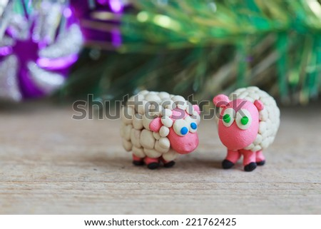 Plasticine world - little homemade white sheep with blue and green eyes stand on a wooden floor, selective focus and place for text - stock photo