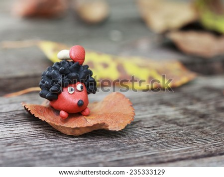Plasticine world - small homemade hedgehog with boletus on his back surrounded by fallen autumn leaves, selective focus on the hedgehog - stock photo
