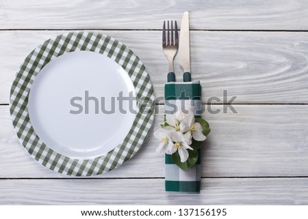 Plate and cutlery decorated with flowers of apple on a wooden table. - stock photo