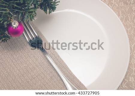 plate and fork on linen tablecloths in a floral pattern and napkin on a table with a Christmas tree decorated with ball - stock photo