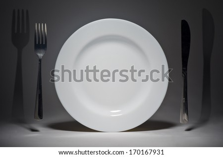 Plate and fork with knife hanging in the air - stock photo