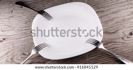 Plate and forks on a wooden background