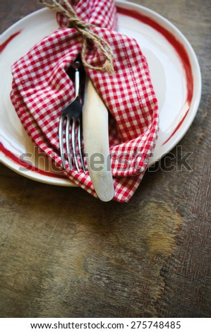Plate and silverware on the old wooden table with burlap and napkin - stock photo