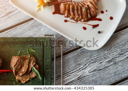 Plate and tray with meat. Cooked meat with sauce. Veal medallions and duck steak. Finest dishes of restaurant menu. - stock photo