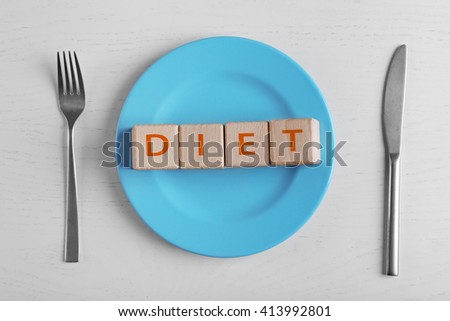 Plate and wooden cubes with text space on white table. - stock photo