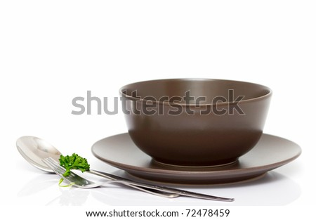 Plate, bowl, spoon and fork with parsley isolated on white (with empty space) - stock photo