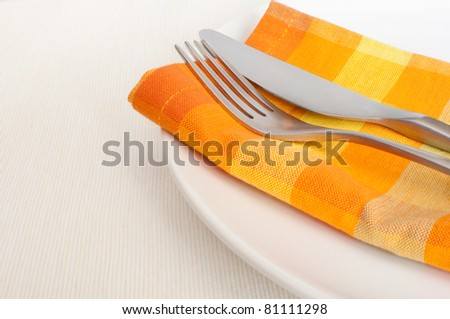 Plate, Cutlery and Orange Napkin on Tablecloth in Restaurant - stock photo