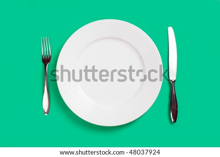 plate fork and knife on green background