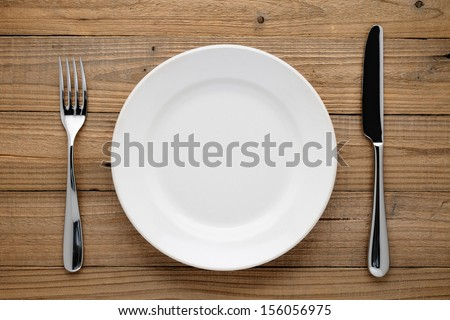 Plate, fork and knife on wooden background - stock photo