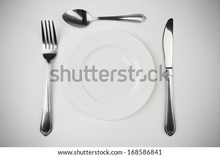 Plate,fork, knife and spoon on white backgrounds - stock photo