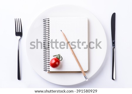 Plate, fork, knife, tomato, pencil and notebook tape on light wooden table