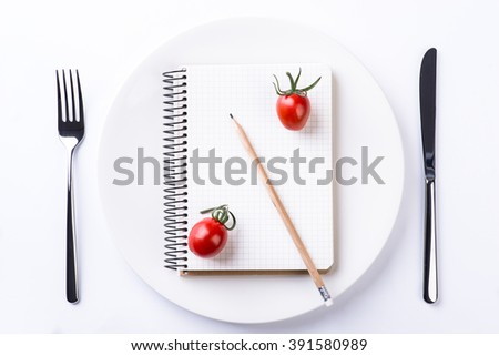 Plate, fork, knife, tomatoes, pencil and notebook tape on light wooden table