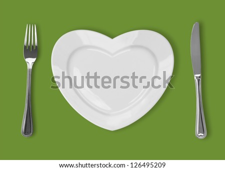 plate in shape of heart, table knife and fork on green background - stock photo
